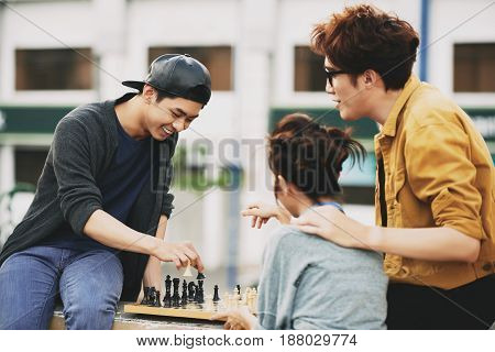 Cheerful young friends having fun while playing chess enthusiastically, apartment house on background