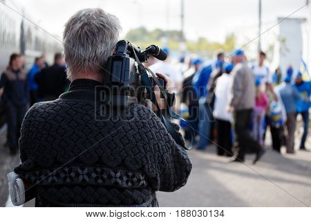 Videographer takes video camera and blur image of people in the background. Professional cameraman covering on event