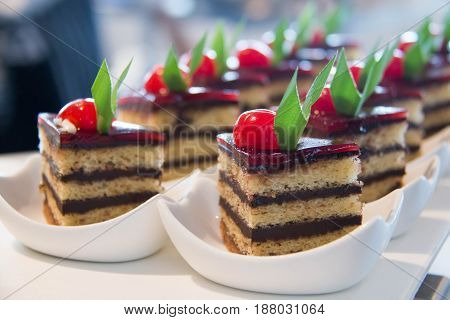 Chocolate mini cakes with cherry on white cup close up
