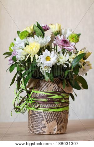 Bouquet of different chrysanthemums in paper with bow on wood.