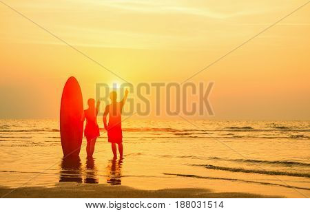 Vacation Concept;Silhouette of happy lovely couple standing at the beach in twilight sunset