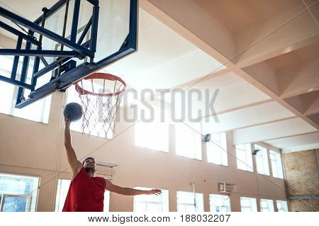 Shot of basketball player slam dunking in the school.