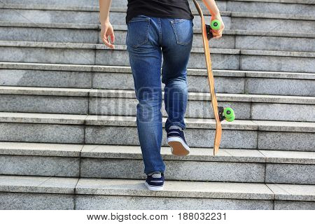 skateboarder with skateboard walking upstairs on city