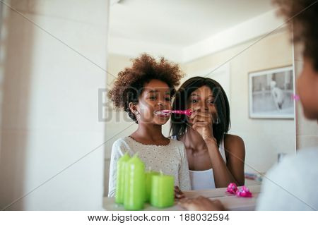 Photo of african american mother and daughter brushing teeth in the morning.