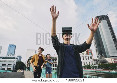 Cheerful teenager using virtual reality headset while walking with friends in city center, waist-up portrait