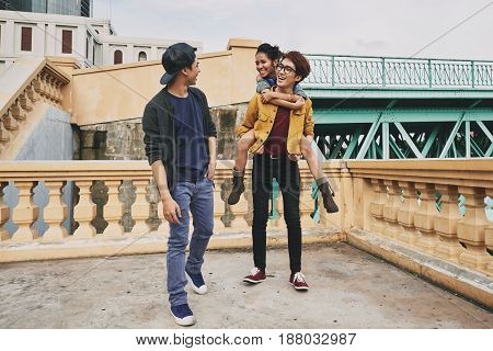 Joyful Asian teenager piggybacking his pretty girlfriend while walking with their friend in city and chatting animatedly
