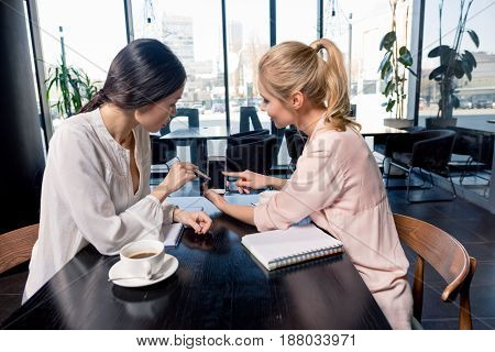 Young Businesswomen Looking At Smartphone With Blank Screen And Discussing Project At Coffee Break