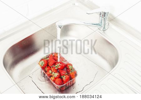 Strawberries are washed in water. Pure fruit is health.