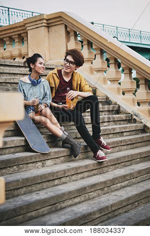 Cheerful Asian skateboarders sitting on shabby stairs, chatting and enjoying soft drinks, full length portrait