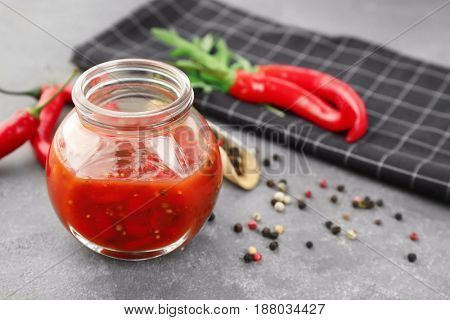 Jar with tasty chili sauce on grey table