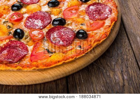 Italian thin pizza with salami pepperoni closeup, pastry with cherry tomatoes and black olives at wooden table background