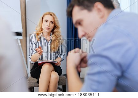 Your diagnosis. Beautiful nice blonde woman holding notes and speaking to her patient while explaining him his diagnosis