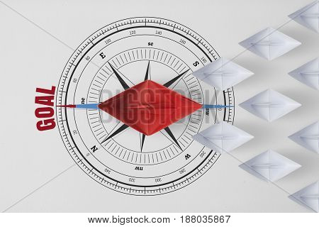 Concept vision leadership goal and workforce leader management with red paper ship on compass needle pointing the red word goal leading among paper ship white.