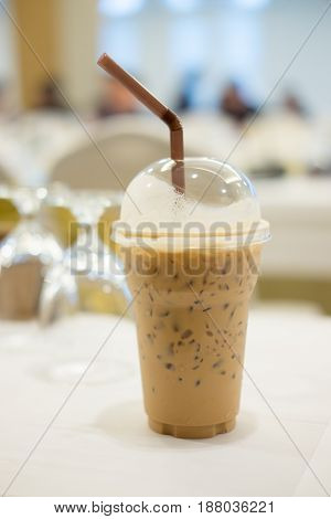 Cold coffee with ice in take away cup in the conference room