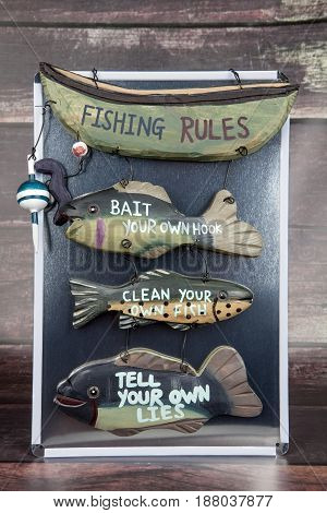 A fishing rules decoration against a wood background