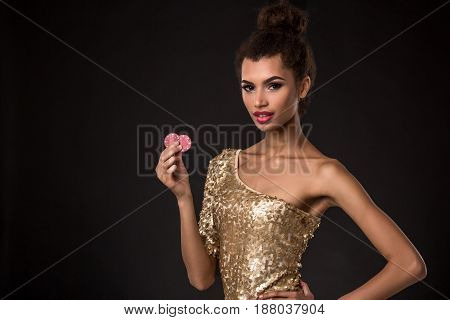 Woman winning - Young woman in a classy gold dress holding two red chips, a poker of aces card combination. Studio shot on black background