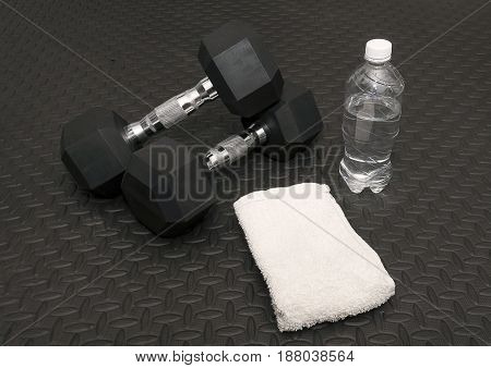 Arm Weights Sweat Towel And Water Bottle On Workout Rubber Mat