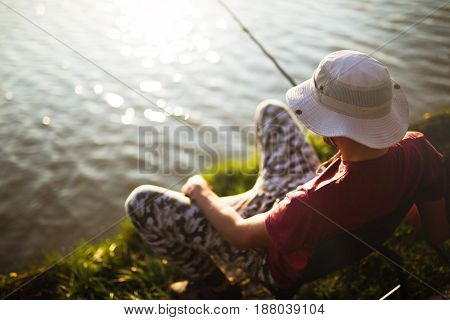 Fishing as recreation and sports displayed by fisherman at lake during sunset