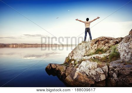 Silhouette of a happy man standing on a rock and arms outstretched against the sky. freedom