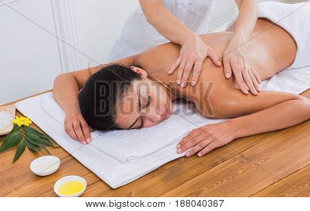 Spa back massage therapy. Masseur make body oil massage to beautiful indian girl in cosmetology cabinet or beauty parlor.