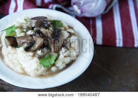 mashed potato with mushroom gravy on black stone slate background