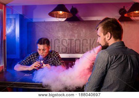 Two young men smoke electronic cigarettes in a vapebar. Vape shop