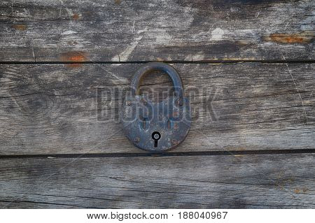 Grungy and rusted steel metal lock on a old wooden boards background. Center position.
