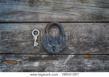 Grungy steel metal key and rusted lock on a old wooden boards background. Center position.
