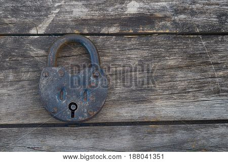 Grungy and rusted steel metal lock on a old wooden boards background. Left position.