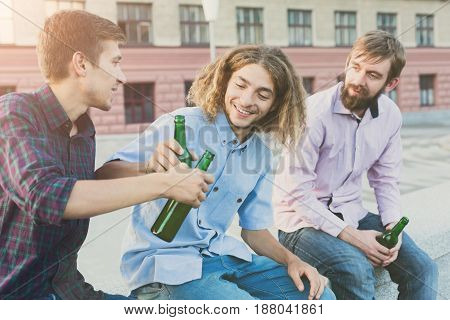 Happy friends cheers with beer outdoor. Company of young man have rest and clinking with bottles. Fun, joy, leisure concept