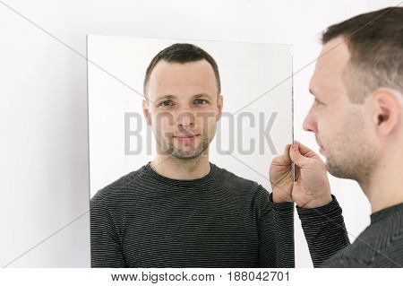 Man Standing Near White Wall With Mirror