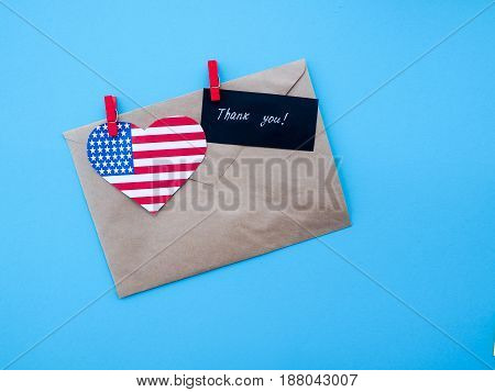 envelope USA flag hanging on colorful pegs clothespin on a line against blue background. United States of America Thank you independence day