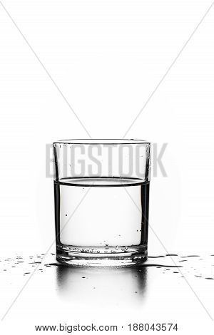 Glass with transparent liquid on a white background