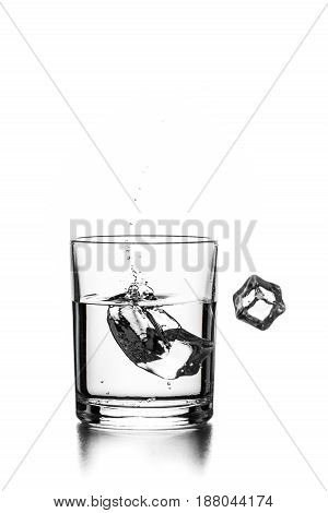 Cube of ice thrown into a glass with transparent liquid