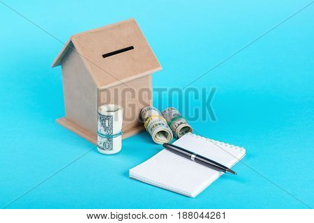The Concept Of Financial Savings To Buy A House. Money Box, Dollars, Notebook With Pen Isolated On B