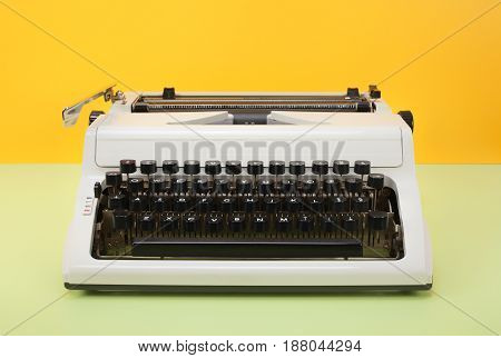 Vintage objects - Retro Typewriter on a yellow background and a green table.