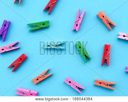 many colored clothespins on a blue background as a substrate pin clothes peg