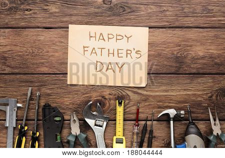 Happy Fathers Day background, card on rustic wood with repair tools and other man things