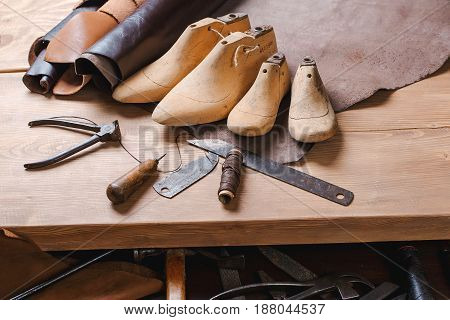 Leather In Rolls, Cobbler Tools And Shoe Lasts In Workshop. Leather Craft Tools.