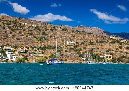 Coast in the village of Elounda. Mirabello Bay. View to the beach from the sea. Several small sailing ships.