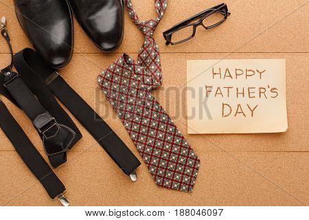 Happy Fathers Day card with male clothes presents, shoes and other man things on cork texture background