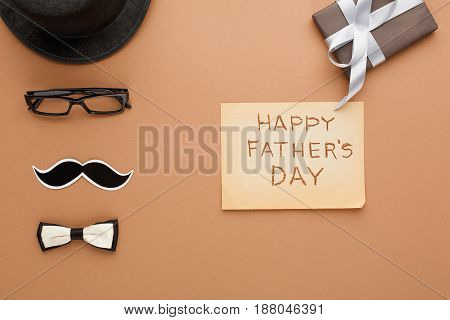 Happy Fathers Day card with male clothes presents, hat, mustache and other man things on beige paper background