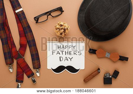 Happy Fathers Day card with male clothes presents, hat and other man things on cork texture background