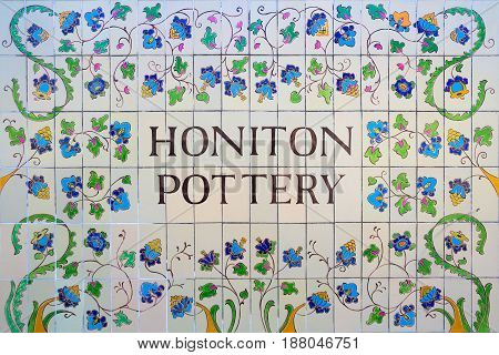 Honiton Devon England - October 10 2016: Ceramic tiles on the wall of one of the houses. Painted with flowers and the inscription - Honiton Pottery.