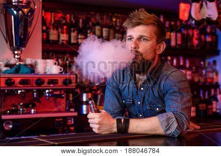Vape. Vaping man in a cloud of vapor. Photo is taken in a vape bar. Vape shop
