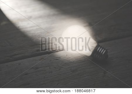 glowing bulb uniqueness concept on brown wooden table