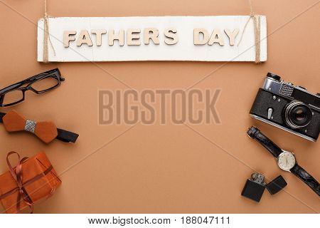 Happy Fathers Day card with male clothes presents, hat and other man things on on beige background