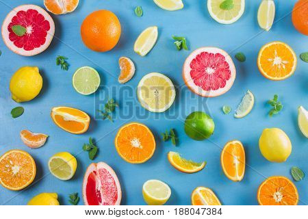 citrus food pattern on blue background - assorted citrus fruits with mint leaves