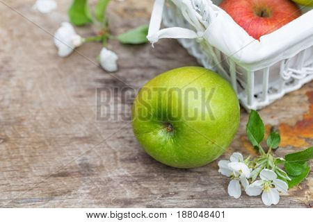 Fresh sweet juicy red and green apples with flowers on a wooden background in garden