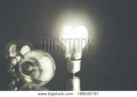 glowing bulb uniqueness concept on black background